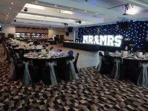 Wedding area set up, wedding tables all decorated and large Mr & Mrs sign lit up at the back of the room. The newly refurbished Blythswood Suite